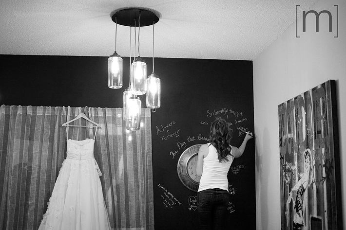 A photo of a wedding dress hanging with friends painting love words