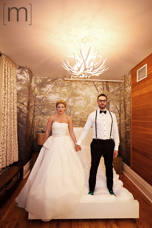 A portait of the bride and groom on the bed at the gladstone hotel