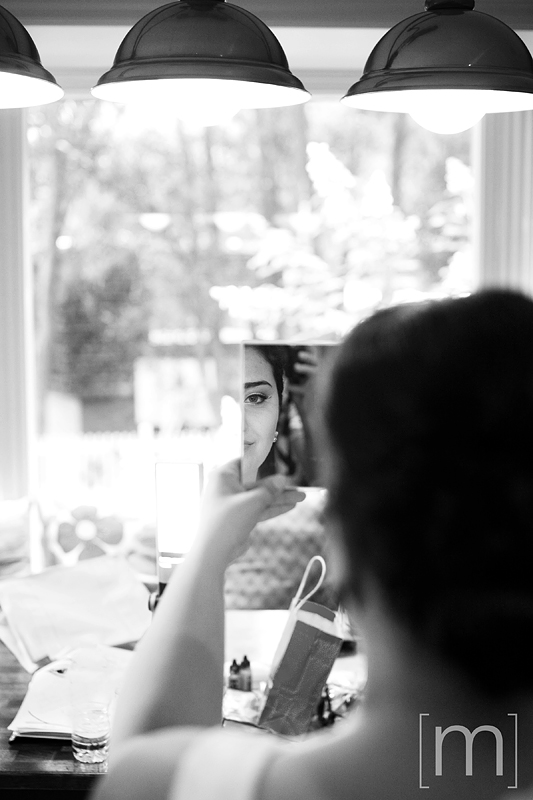 a photo of the bride looking in the mirror as she gets ready