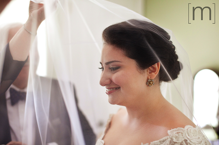 a photo of the happy bride getting veiled as she gets ready