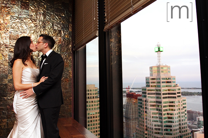A photo of a the bride and groom at window at canoe restaurant