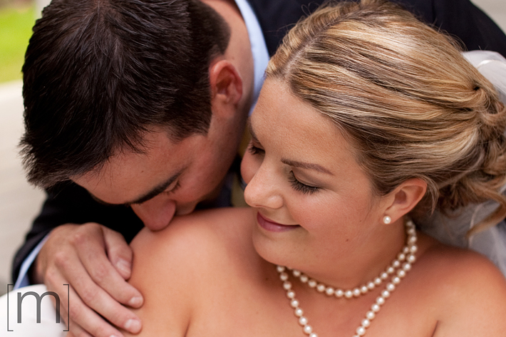a photo of a groom kissing bride's shoulder at erchless estate in oakville