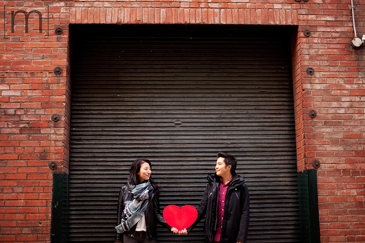 a photo of a couple holding a heart at an e-shoot at liberty village toronto