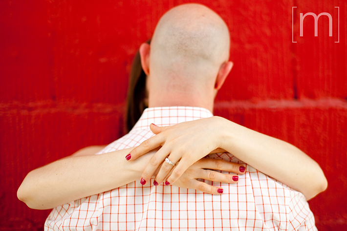 a photo of a couple against a red wall at an eng shoot at wychwood barns