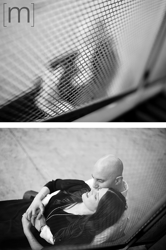 a photo of a couple shot through a fence at an eng shoot at wychwood barns