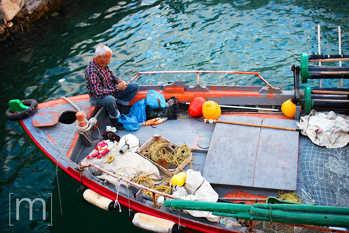 a travel photo of a man fishing in crete greece
