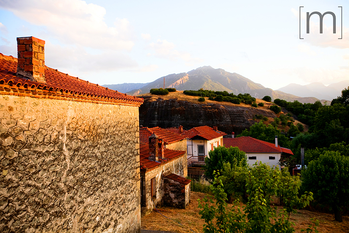a travel photo of terracotta roof at sunset in meteora greece
