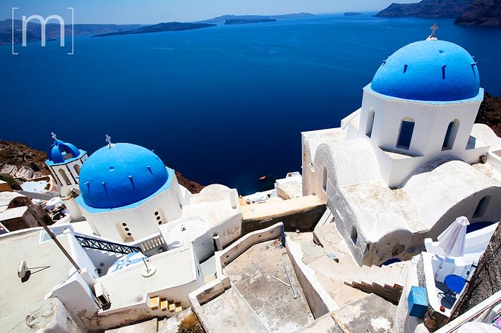 a travel photo of church domes in santorini greece