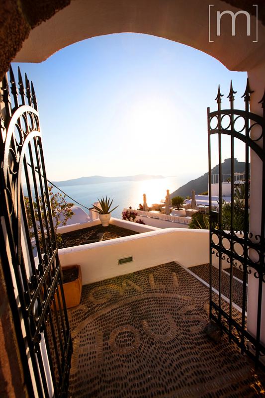 a travel photo of the doorway to heaven in santorini greece