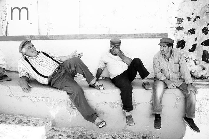 a travel photo of men relaxing in santorini greece