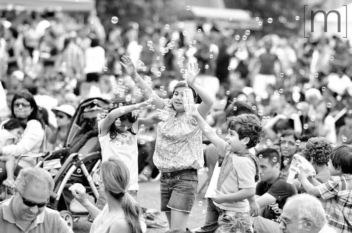 a photo of a child blowing bubbles at a canada day event in mississauga
