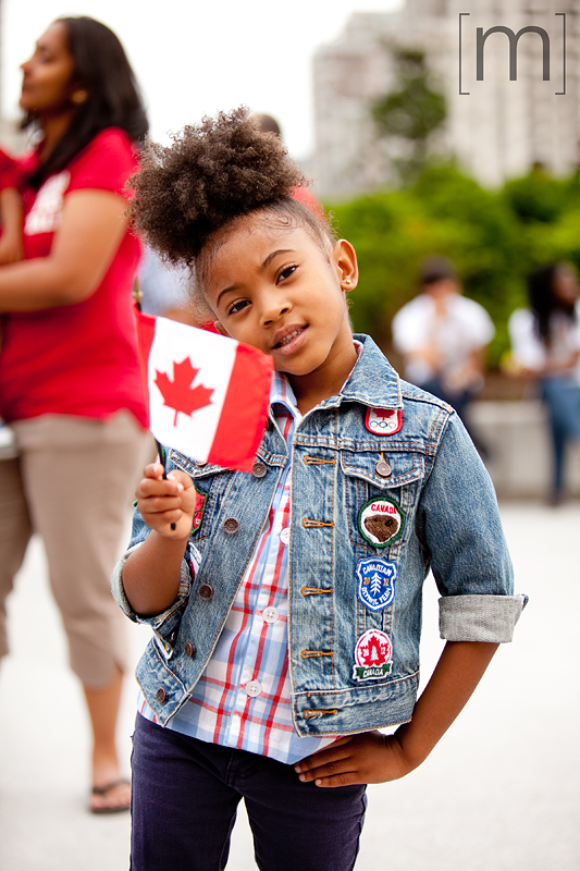 a photo of a child holding flag at a canada day event in mississauga