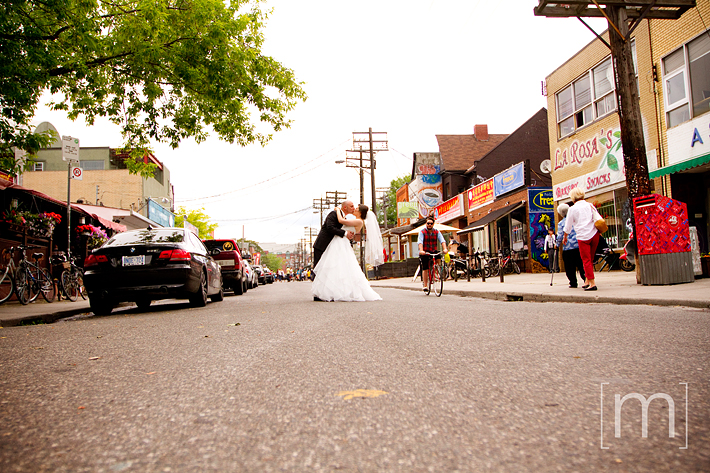 a photo of a bride and groom kissing in kensington market toronto