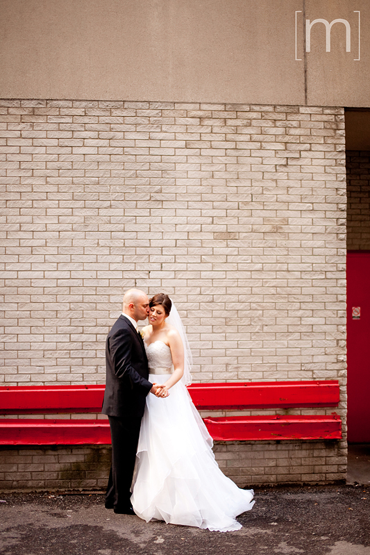 a photo of a bride and groom against red wall at pangaea restaurant toronto