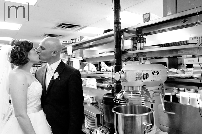 a photo of a bride and groom kissing in the kitchen at pangaea restaurant toronto
