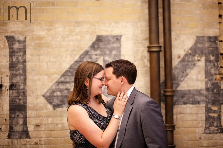 a photo of a couple against a brick wall at an engagement shoot in toronto
