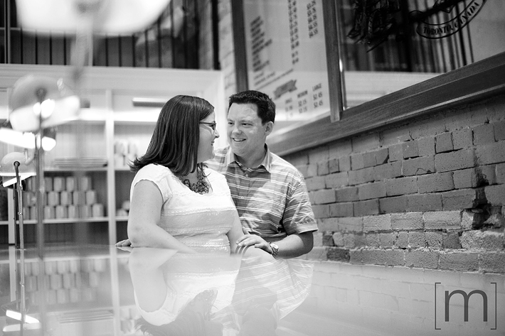 a photo of a couple laughing at an engagement shoot at a coffee shop toronto