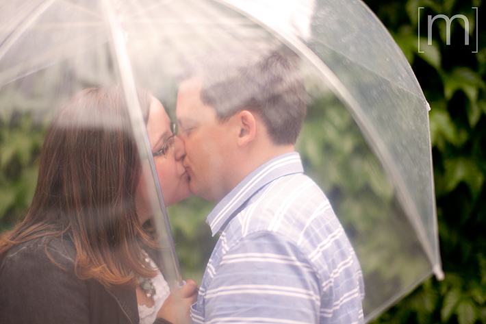 a photo of a couple with an umbrella at an engagement shoot at a park in toronto