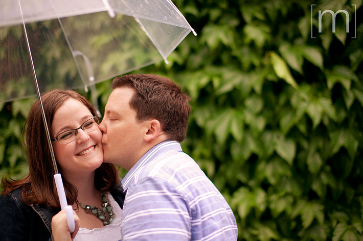 a photo of a couple with umbrella vines at an engagement shoot at a park in toronto