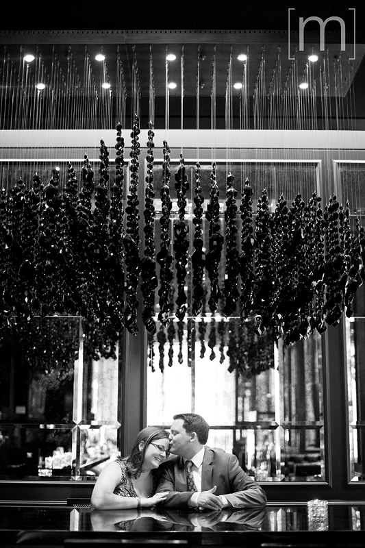 a photo of a couple with cool light fixture at an engagement shoot at the trump tower in toronto