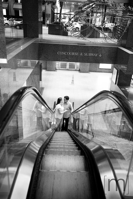 a photo of a couple on the escalator at an engagement shoot at the trump tower in toronto