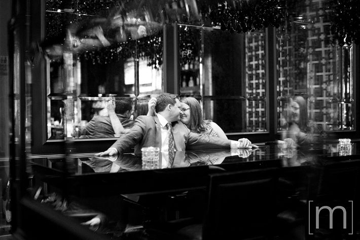 a photo of a couple against reflection at an engagement shoot at the trump tower in toronto