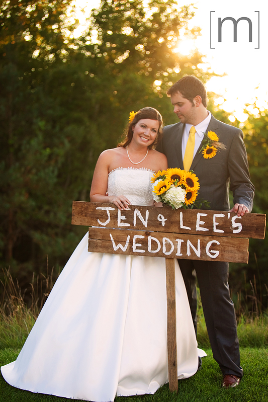 a photo of a couple with a wooden sign at sunset at a wedding at wooden sticks uxbridge