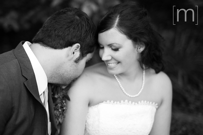 a photo of the groom kissing the bride on the shoulder at a wedding at wooden sticks uxbridge