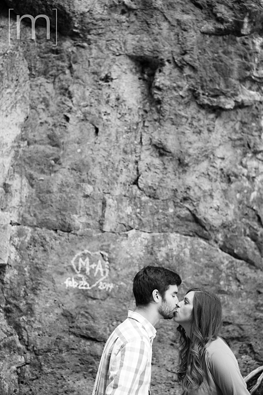 a photo of a couple kissing in front of rocks with heart sign at an engagement shoot in rockwood