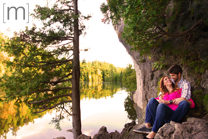 a photo of a couple sitting beside calm lake at an engagement shoot in rockwood