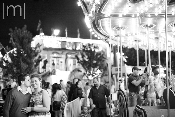 a photo of a couple beside carousel at an engagement shoot at the cne toronto