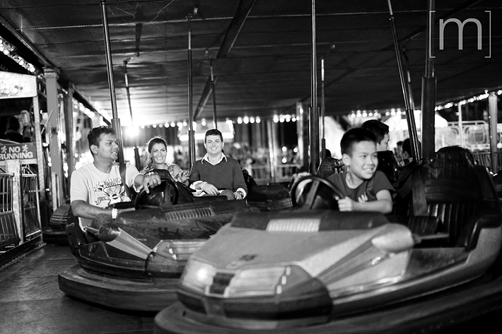 a photo of a couple on bumper cars at an engagement shoot at the cne toronto