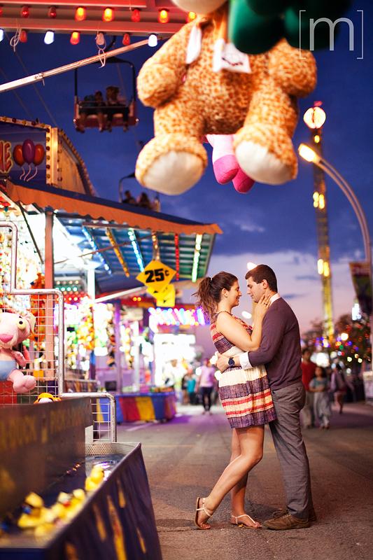 a photo of a couple hugging at night at an engagement shoot at the cne toronto