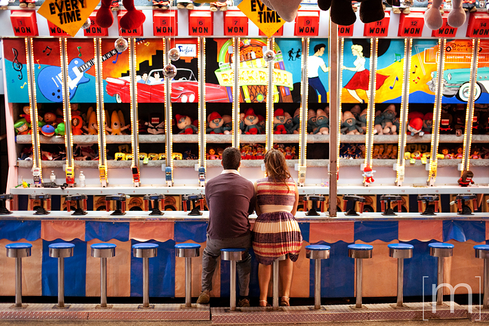 a photo of a couple playing games at an engagement shoot at the cne toronto