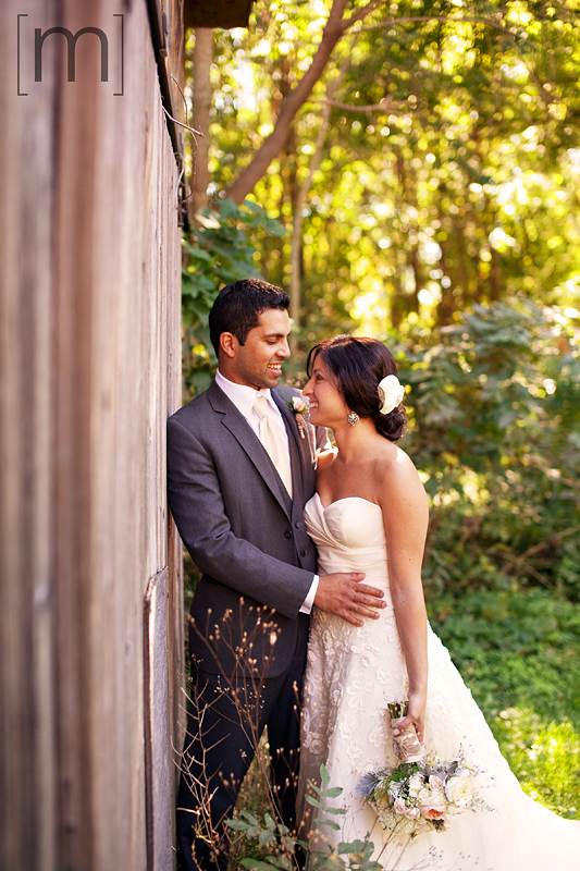 a photo of a couple cuddling against a barn at a wedding in niagara on the lake