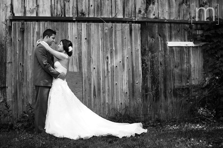 a photo of a cute couple against a barn at a wedding in niagara on the lake