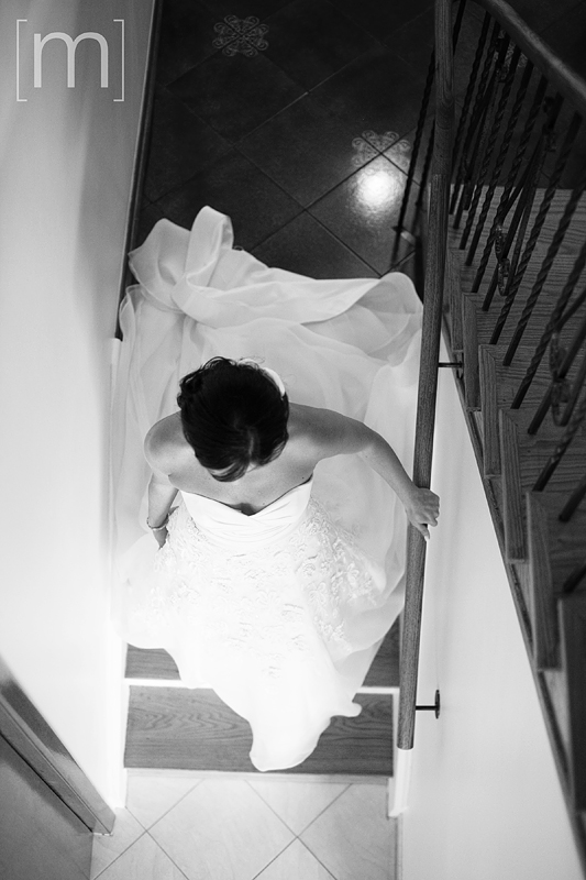 a photo of a bride walking down the stairs at a wedding in niagara on the lake