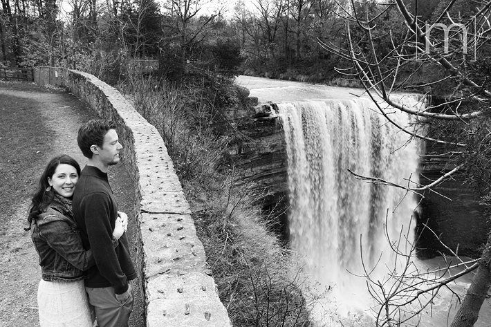 a photo of a couple cuddling beside balls falls at fall engagement photoshoot