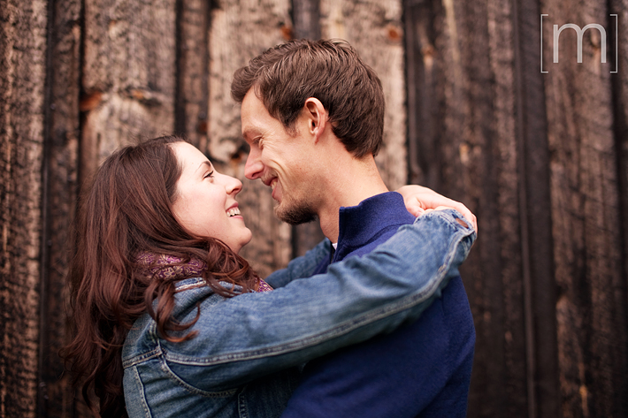 a photo of a couple cuddling against a rustic barn at a fall engagement photoshoot in balls falls