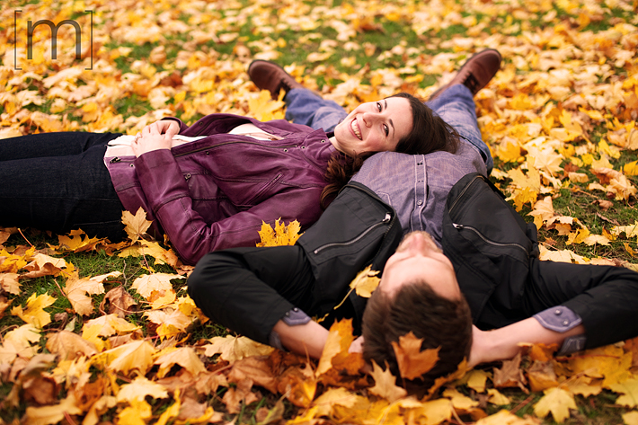 a photo of a couple laying down in a colourful forest at a fall engagement photoshoot in balls falls