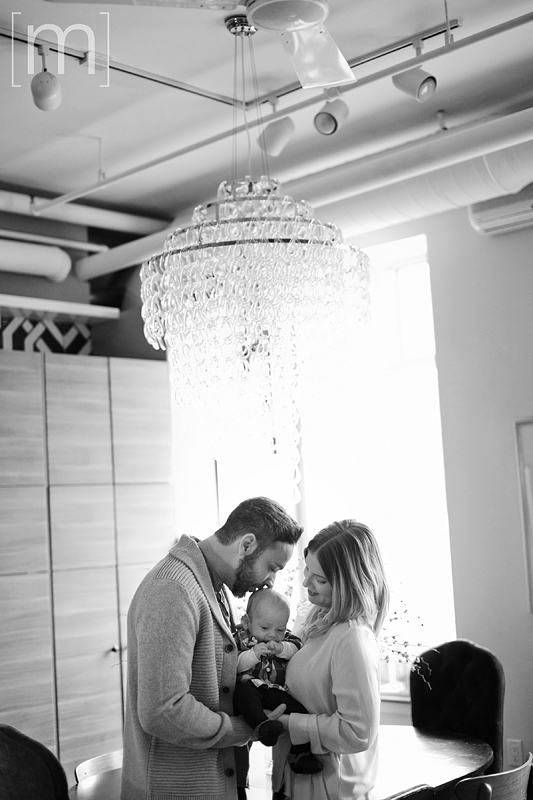 a photo of a couple kissing their newborn on the head at a family photoshoot in toronto