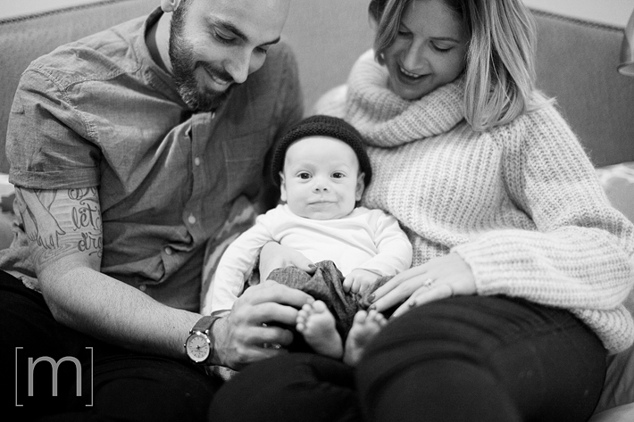 a photo of a couple on a bed with their smiling newborn at a family photoshoot in toronto