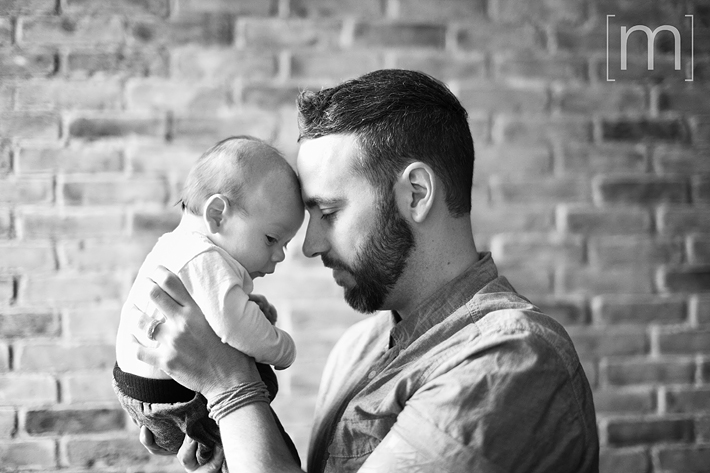 a photo of a father cuddling his newborn at a family photoshoot in toronto