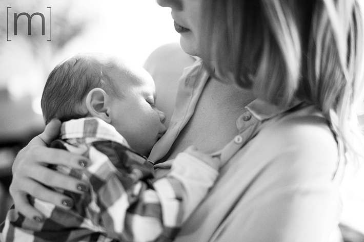 a photo of a mother holding her sleeping newborn at a family photoshoot in toronto