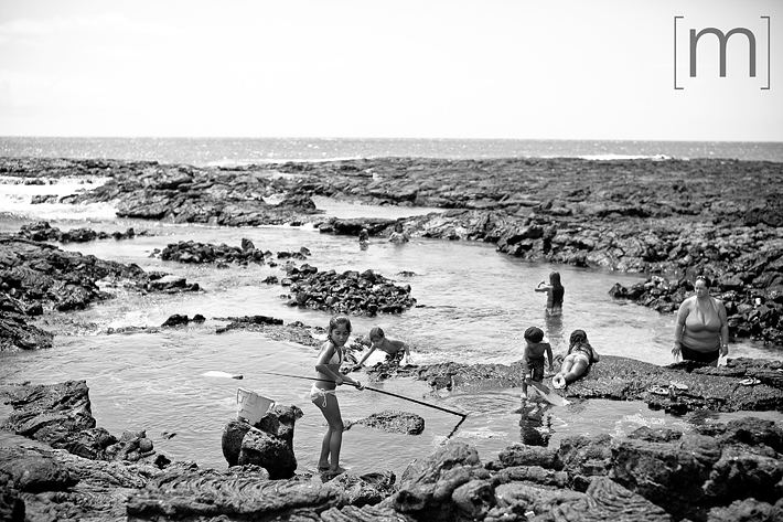 a travel photo of the big island family on rocky beach in hawaii