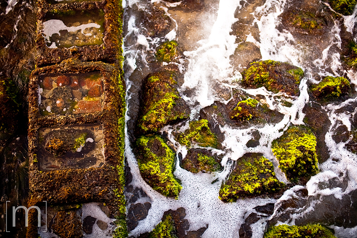 a travel photo of green rocks on the beach in oahu hawaii