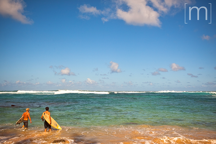 a travel photo of surfers on a turquoise beach on the northshore in oahu hawaii