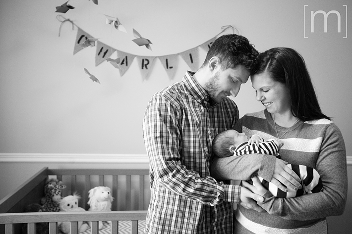 a photo of a couple cuddling their baby at new born photoshoot in hamilton
