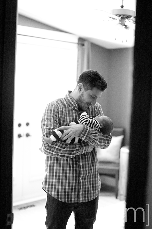a photo of a father holding a newborn at a photoshoot in hamilton