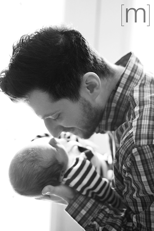 a photo of a father kissing a newborn at a photoshoot in hamilton